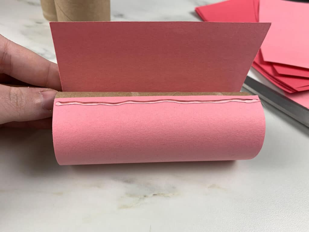 Construction paper and hot glue around toilet paper roll
