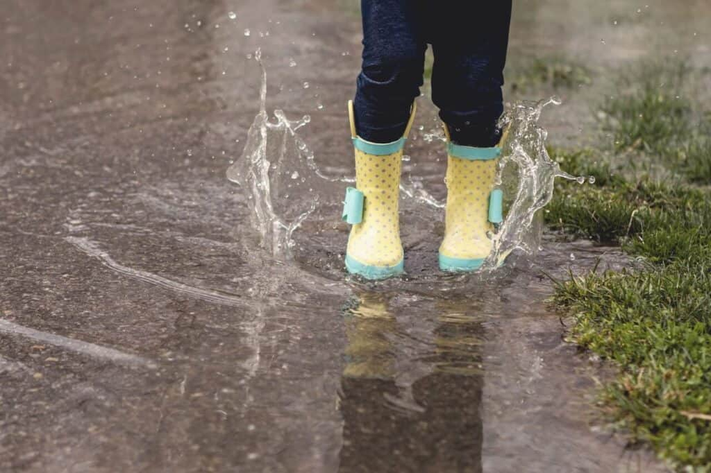 Feet splashing in rain puddles with rain boots