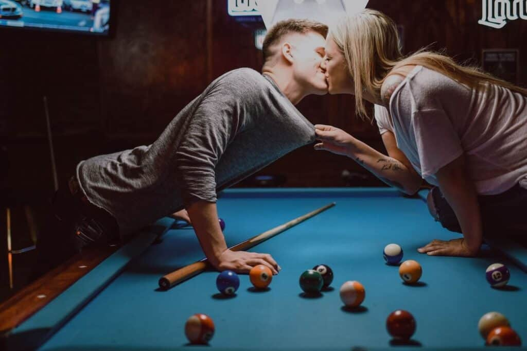 Couple kissing on a pool table for things to do on a rainy day for adults