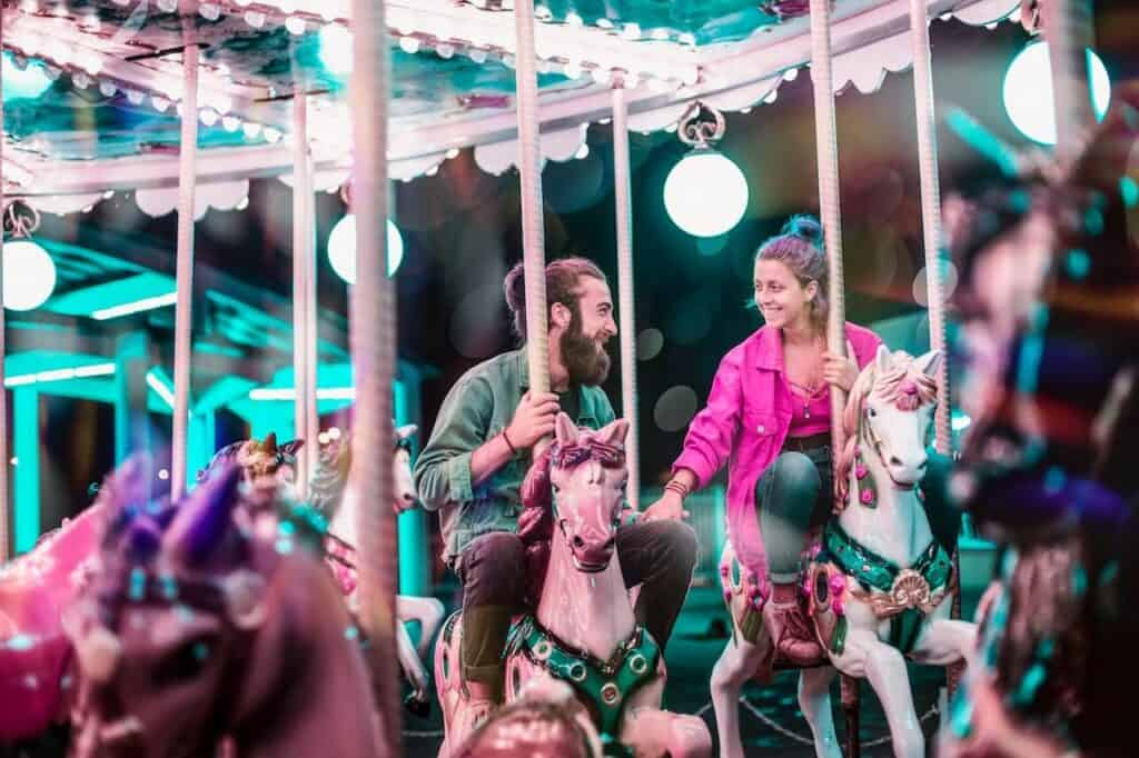 Couple riding carousel in mall