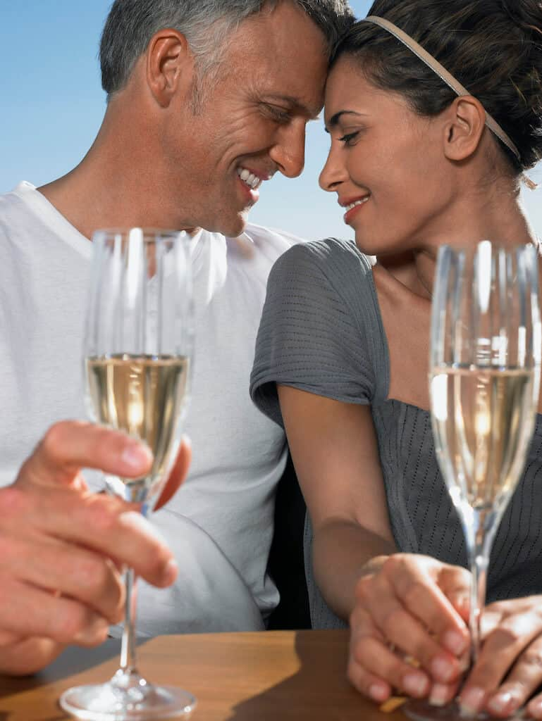Couple holding champagne glasses at a winery outdoor date