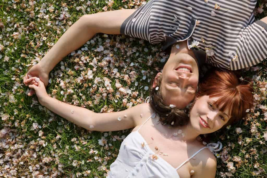 couple laying in the grass with flower petals all around