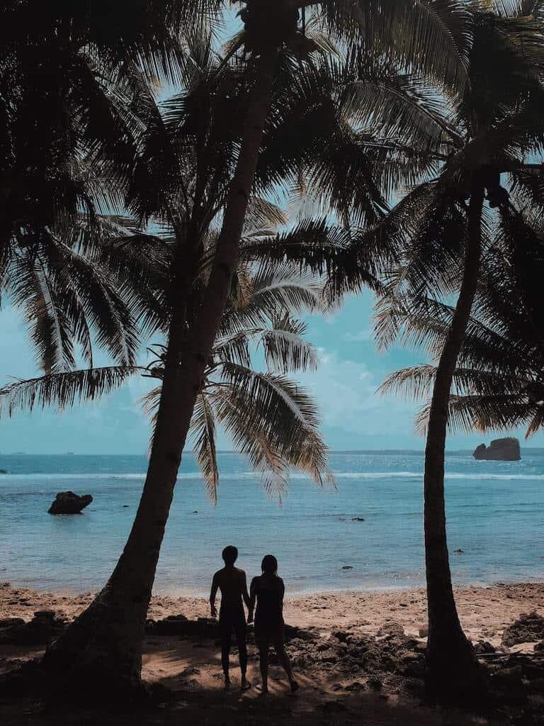 couple standing under palm trees at beach summer bucket list