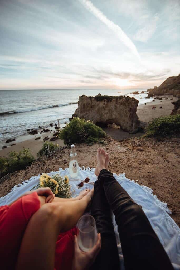 Couple sitting on blanket on the beach