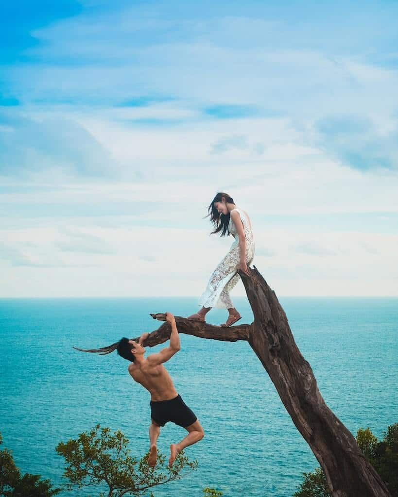 couple climbing on a tree by the ocean