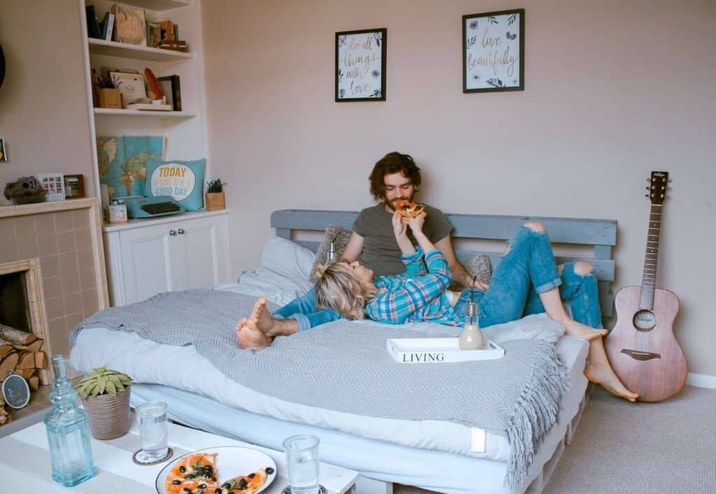 couple laying in bed eating pizza for at home date idea