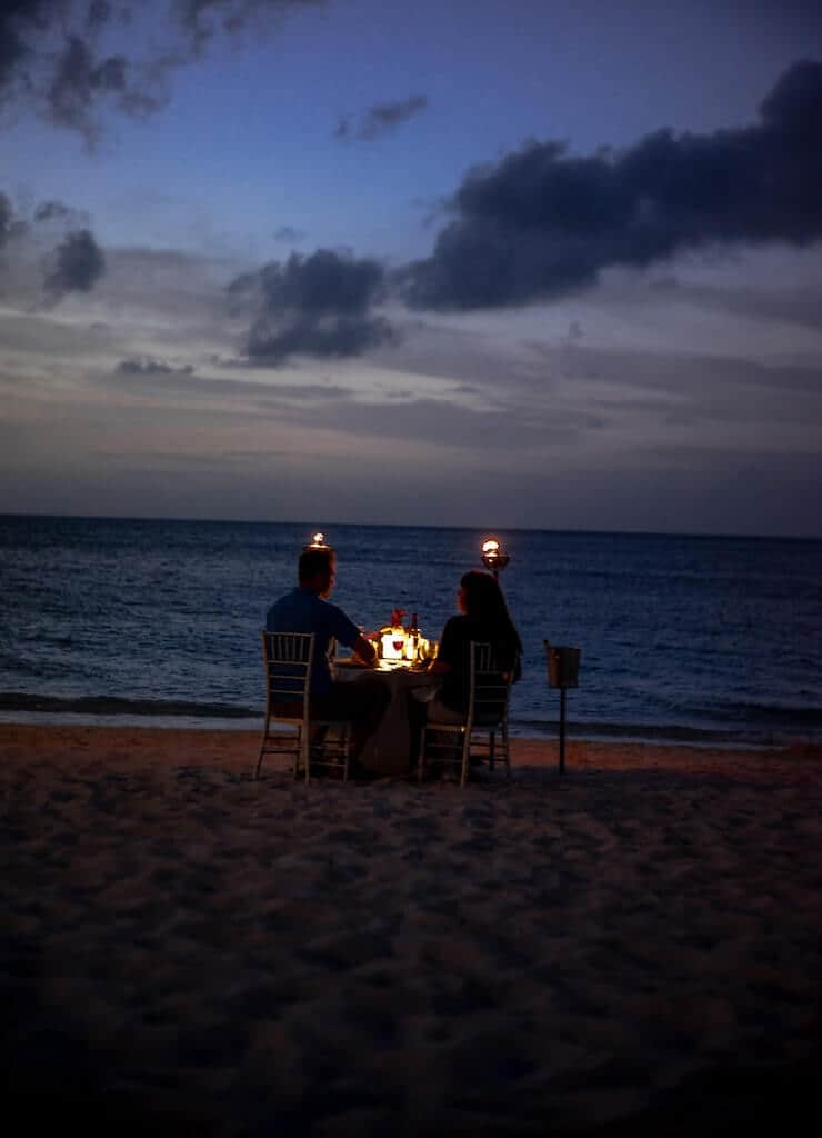 couple having a candle lit dinner for their wedding anniversary celebration