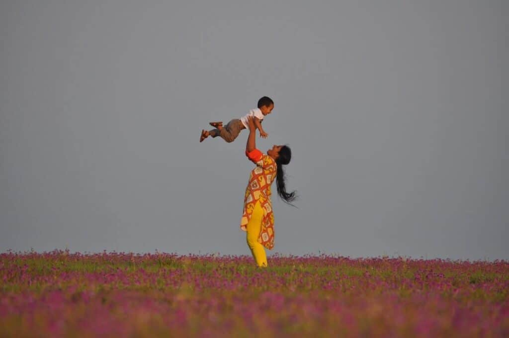 woman holding son up in air in a flower field