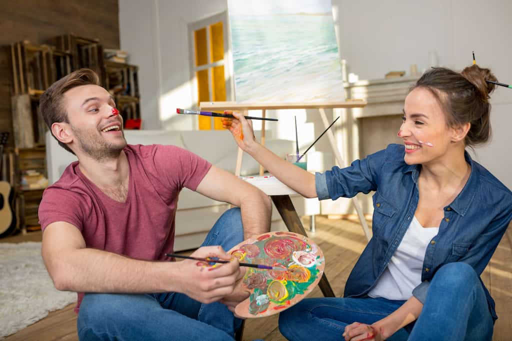 couple painting together for date night with paint on noses
