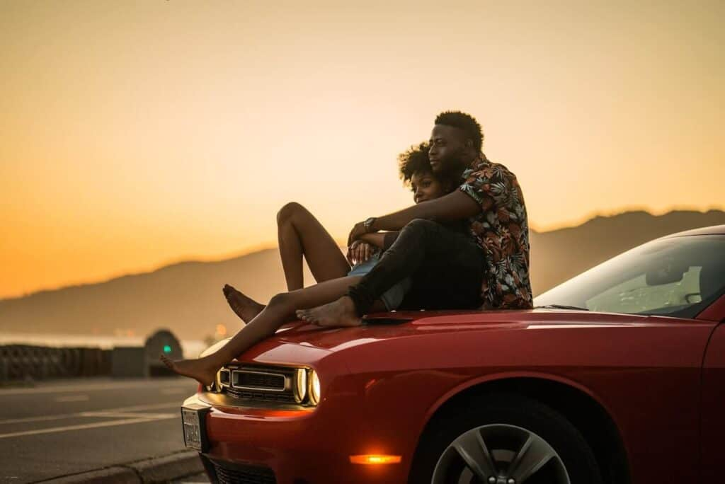couple sitting on hood of car watching the sunset