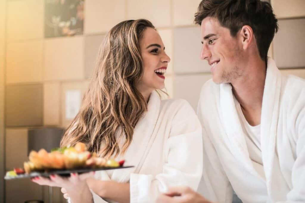 couple in robes with a food plate smiling at each other