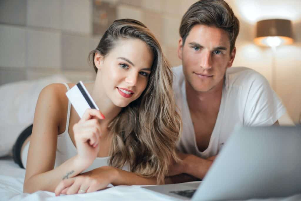 woman holding credit card next to man with computer