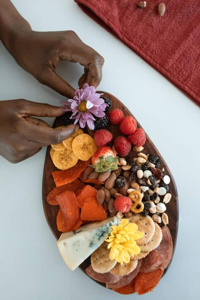 flatlay of a charcuterie board with hands placing a flower on the corner