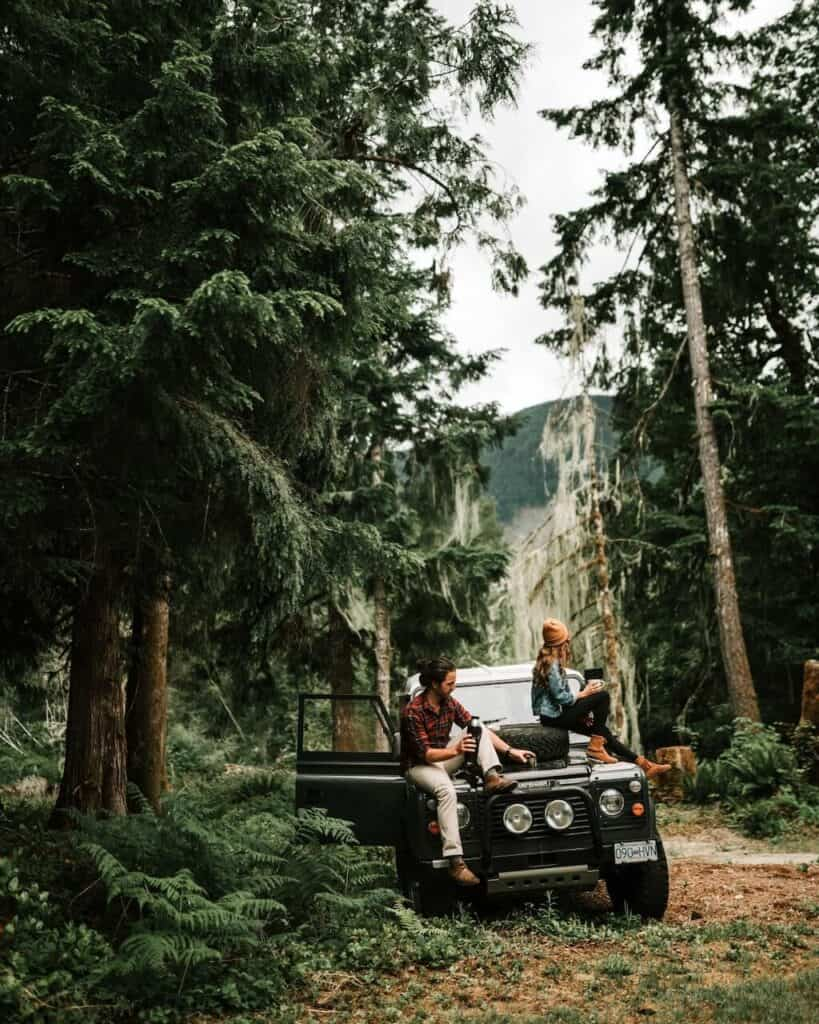 couple sitting on hood of car in the forest with cups of coffee