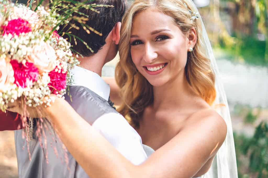 bride hugging groom and smiling at camera