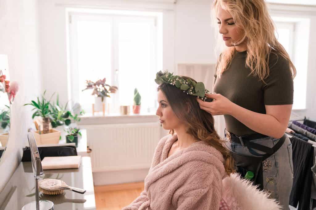 hairdresser putting a flower crown on a bride