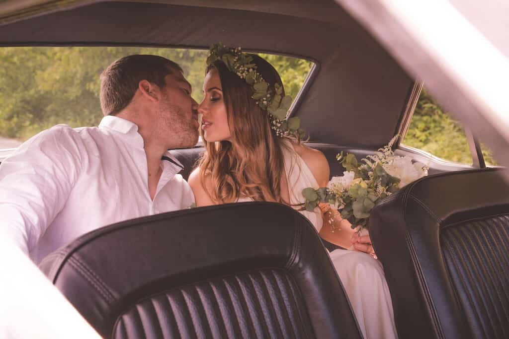 couple sitting in a backseat of the car about to kiss