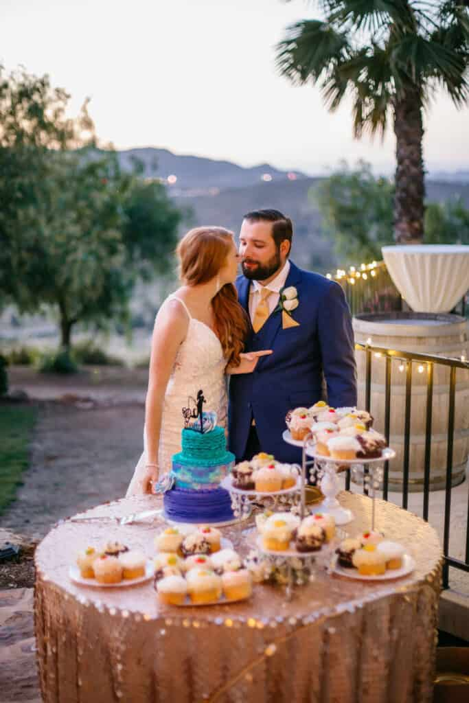 bride and groom at cake table with wedding cake and cupcakes from Sams club
