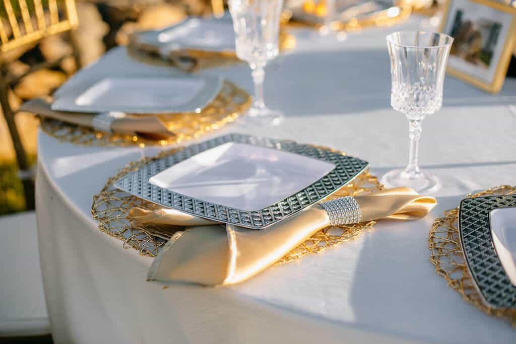 silver plastic plates on a table at wedding reception