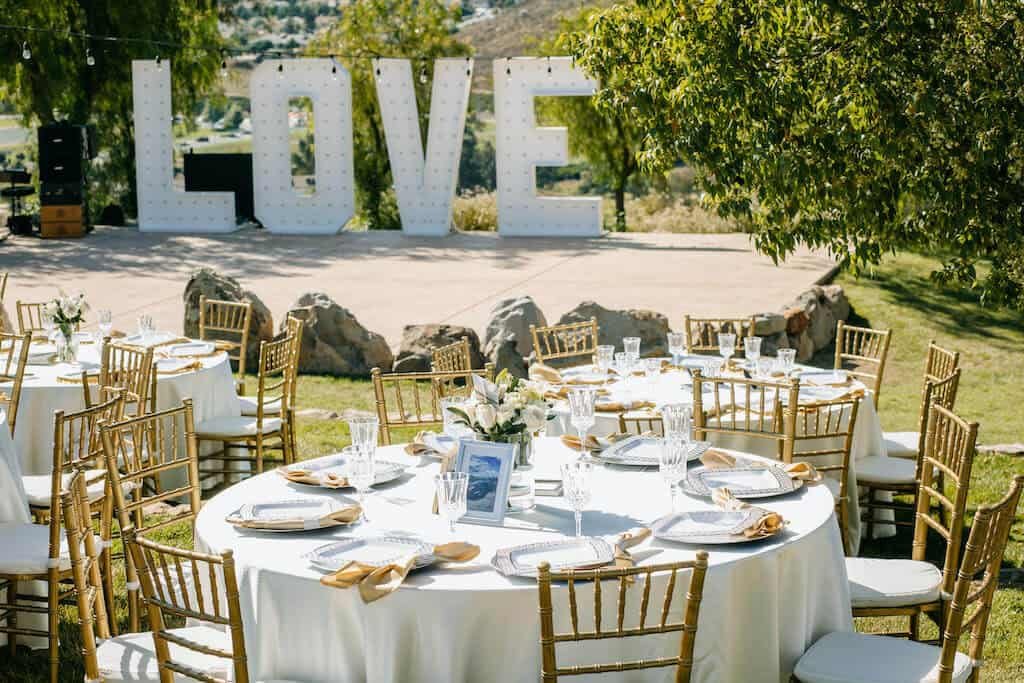 wedding reception with tables set and LOVE sign in background