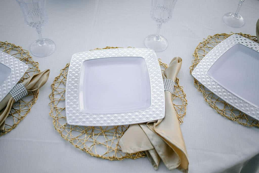 table setting with plastic wedding plates, placemat, and napkins