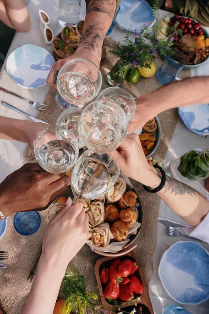 wine glasses clinking over a table of food