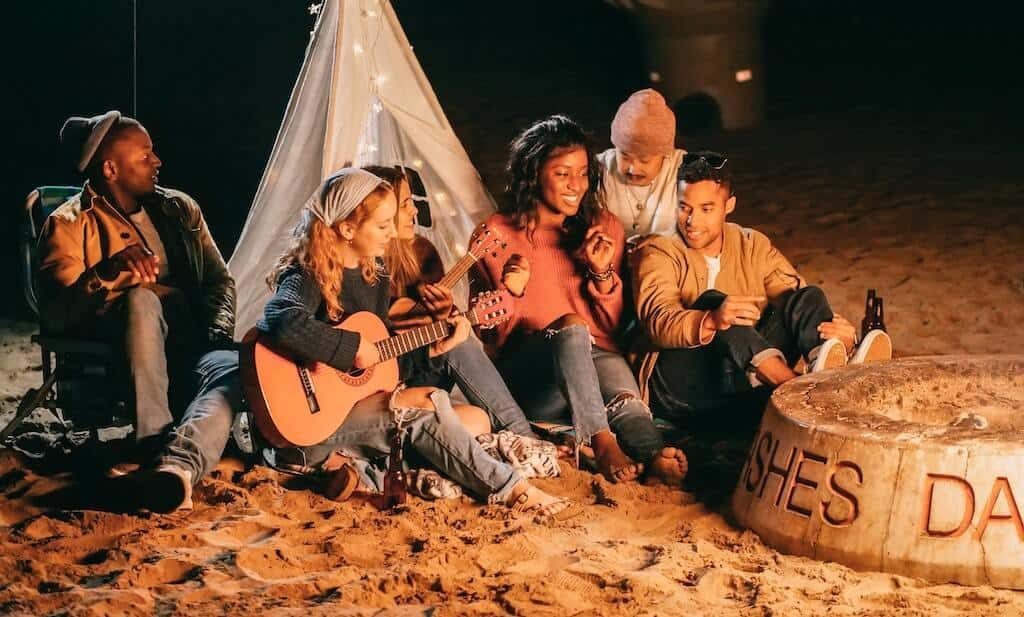 group of friends sitting on a beach next to a fire and playing a guitar in front of a tent