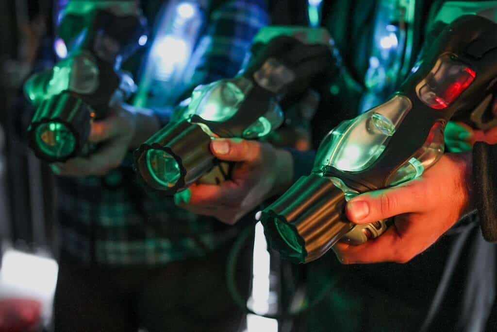 three hands holding laser tag guns on a double date