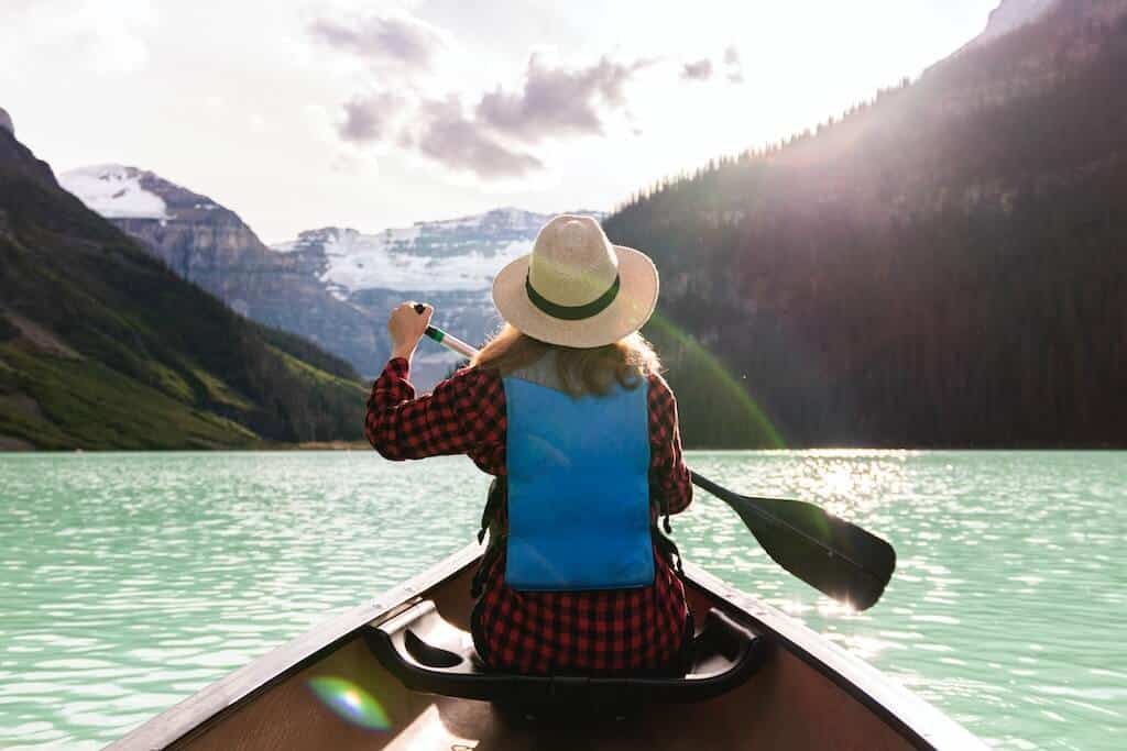 woman sitting in paddle boat looking at mountains for cute date ideas